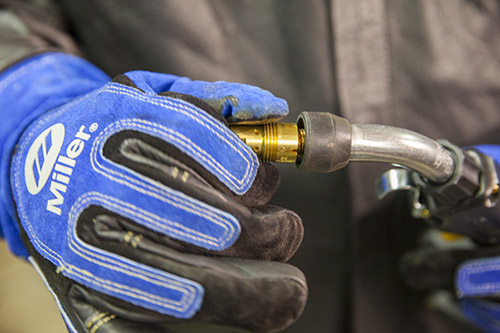 Image of welder with gloves, starting to take off a nozzle on a MIG gun