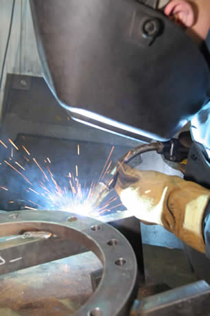 Image of a welder leaning over welding with a MIG gun.