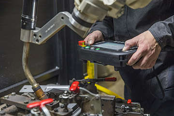 Image showing weld operator with a teach pendant in a robotic MIG welding cell