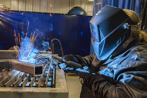 Image of a person welding while their MIG gun is overheating