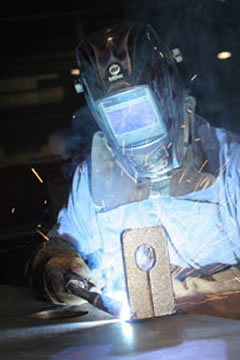 Image of a welder in a shop welding with a MIG gun