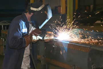 Image of a welder looking closely at an arc with MIG gun in hand