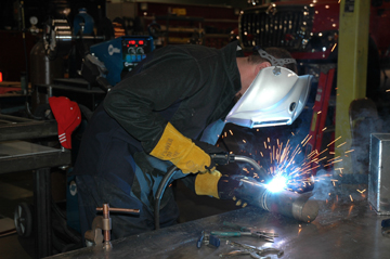 Image of welder leaning over to see the weld contact tip more closely