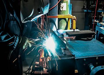 Welder bent over MIG welding part on table