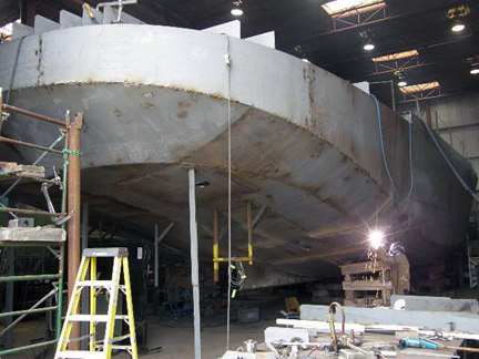 Image of a boat being manufactured and a welder at the base of the huge boat welding