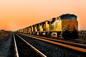 Yellow train on the tracks with many railcars behind