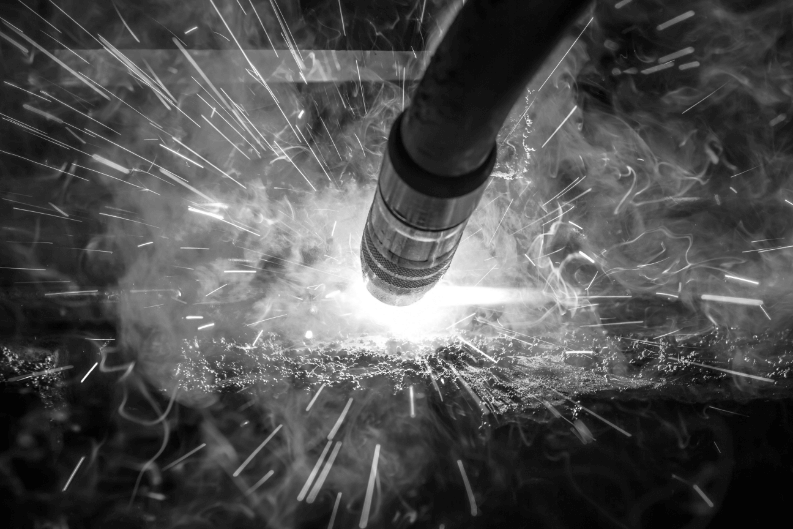 Black and white image of MIG Gun welding with sparks