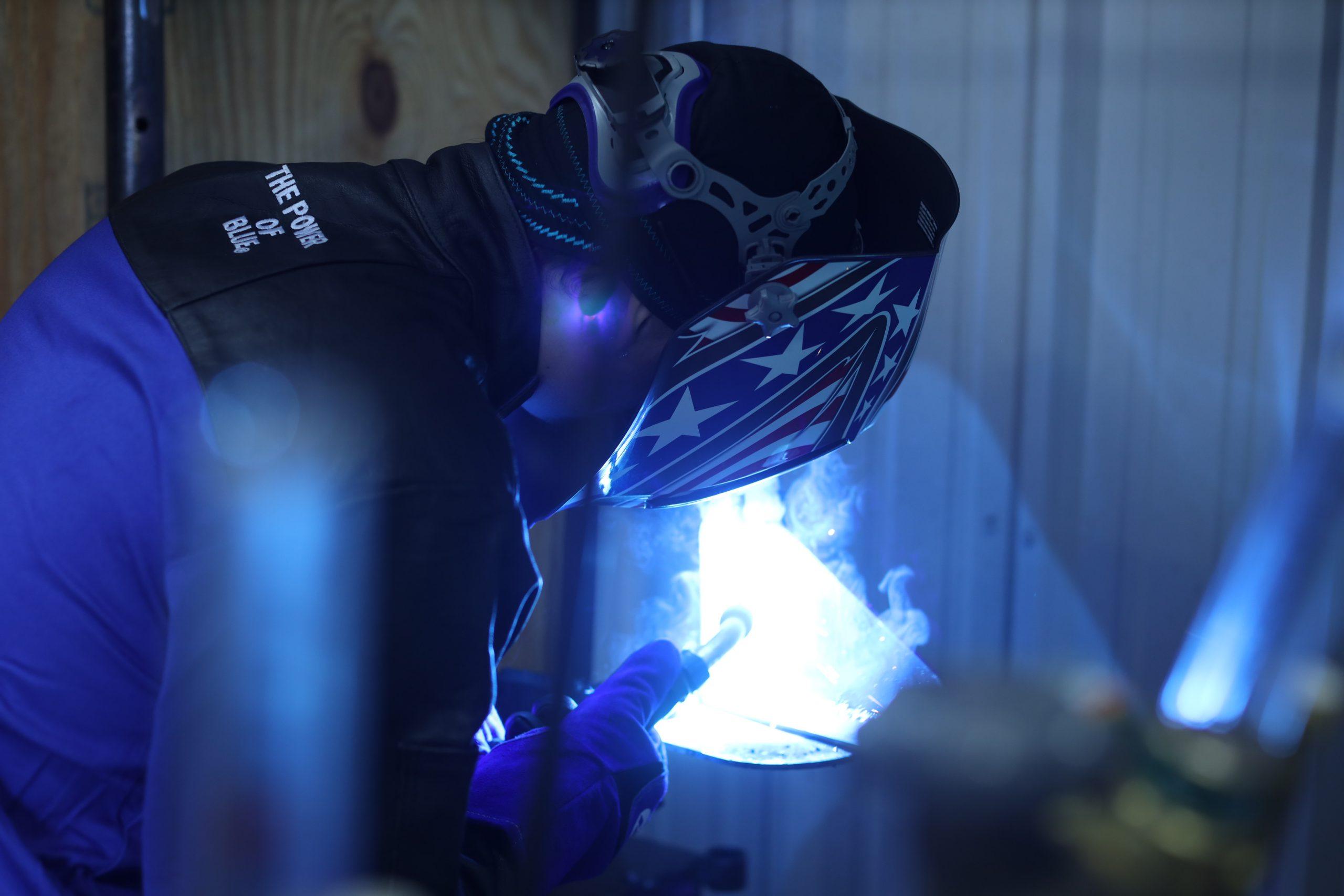Welder welding with a stars and stripes helmet, Miller welding jacket
