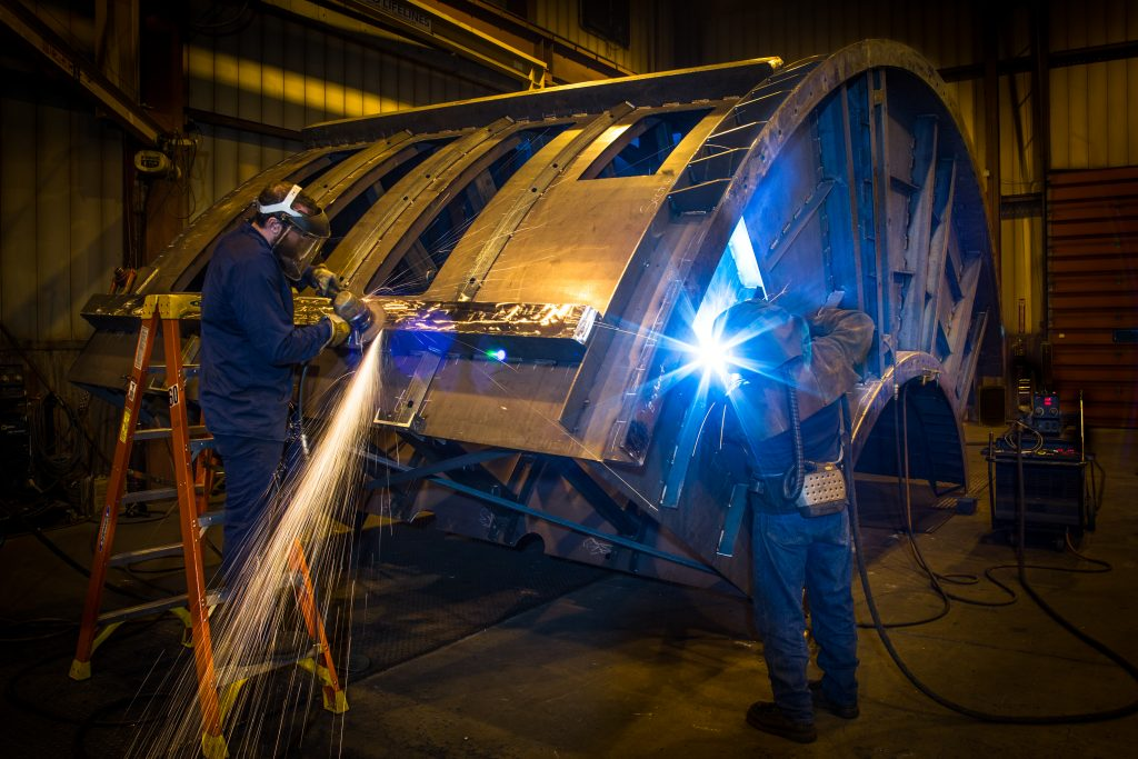 Welding operator welding on large piece of vibrating equipment with another person grinding