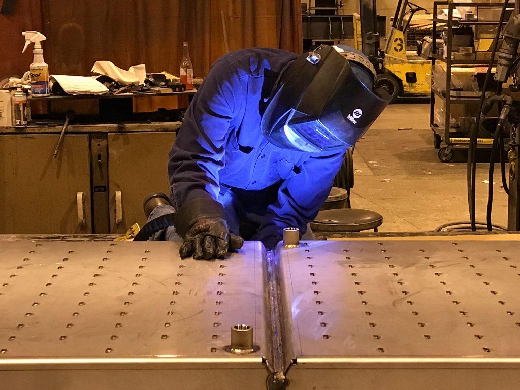 Welding operator welding the underside of a flat piece of metal