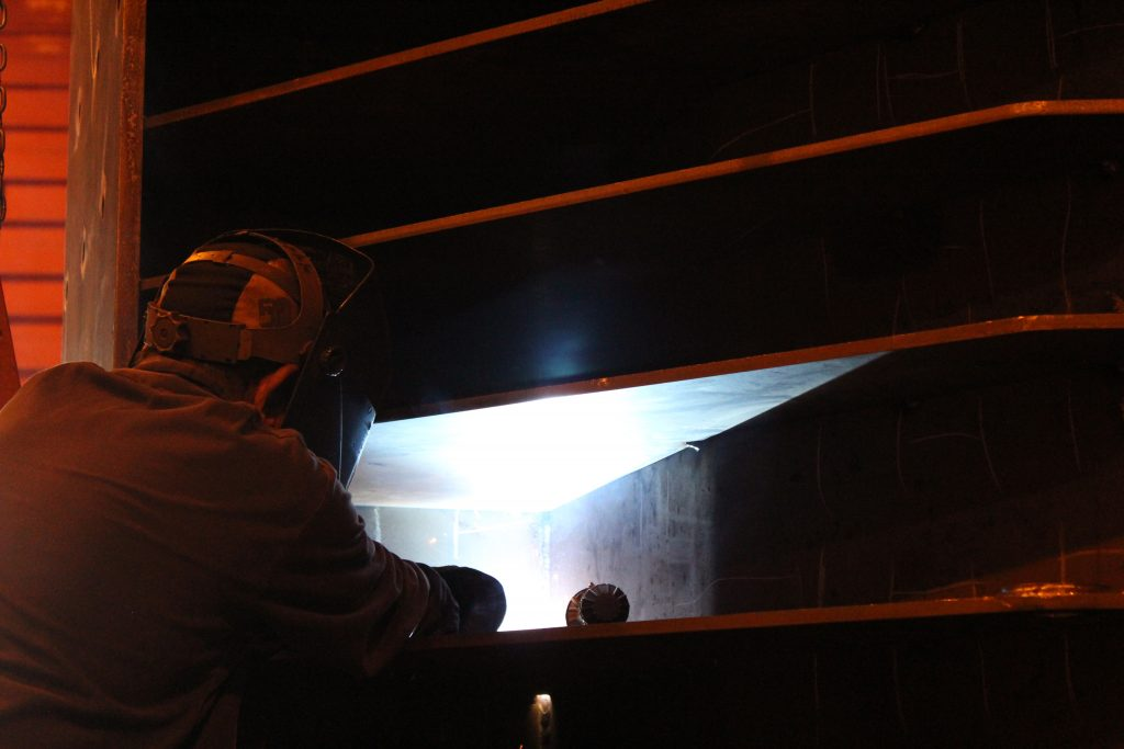 Over-the-shoulder view of welding operator welding on large piece of equipment